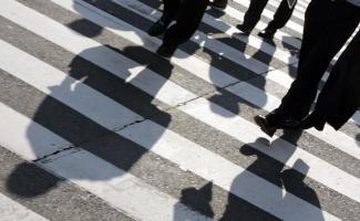 Businessmen cast shadows as they cross a street in Tokyo's Marunouchi district July 25, 2007. The Japanese government will release preliminary gross domestic product (GDP) data for the April-June quarter on August 13, the Cabinet Office said, just ahead of central bank review at which it is expected to raise rates. REUTERS/Yuriko Nakao (JAPAN) - GM1DVTXXVFAA
