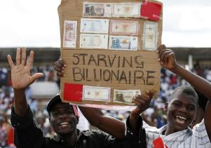 Zimbabwe opposition Movement for Democratic Change (MDC) supporters show old worthless bank notes at an election rally in Chitungwiza, near the capital Harare, March 27, 2008. REUTERS/Howard Burditt (ZIMBABWE) - GM1E43S02A201