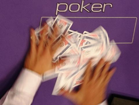 A dealer shuffles playing cards on the table at the World Series of Poker Europe competition at the Empire Casino in London October 1, 2008. REUTERS/Luke MacGregor (BRITAIN) - LF3E4A1182401