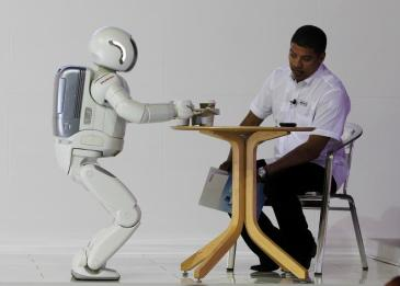 ASIMO, a humanoid robot created by Honda, serves tea to a visitor during the Johannesburg International Motor Show at Nasrec in Johannesburg, October 6 2011.REUTERS/Siphiwe Sibeko (SOUTH AFRICA - Tags: SCIENCE TECHNOLOGY BUSINESS SOCIETY TPX IMAGES OF THE DAY) - GM1E7A707YH01