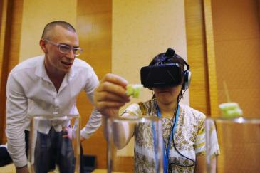"""Dan Garrett of the Royal College of Art and Imperial College London watches as a visitor tastes food using Tasteworks technology, a Virtual Reality experience that augments and stimulates taste, during a design competition showcase of wearable technology at the Augmented Human International Conference in Singapore March 10, 2015. The conference runs from March 9 to 11. Tasteworks was developed from a study of dementia patients' communication difficulties. Such patients with deteriorating recognition capabilities may find eating stressful and unenjoyable. Using Oculus Rift and Leap Motion technology, Tasteworks places the subject in a """"hyper realistic Virtual World"""" where flavour can be generated and emphasized. REUTERS/Edgar Su (SINGAPORE - Tags: SCIENCE TECHNOLOGY BUSINESS) - GM1EB3A1FDC01"""