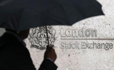 A man shelters under an umbrella as he walks past the London Stock Exchange in London, Britain August 24, 2015. World stock markets plunged on Monday, as a near 9-percent dive in China shares and a sharp drop in the dollar and major commodities sent investors rushing for the exit. The Dow Jones Industrial Average dropped more than 1,000 points as Wall Street opened, and the benchmark Standard & Poor's 500 index slid more than 2.5 percent, a drop that puts it nearly 10 percent below its record high. REUTERS/Suzanne Plunkett - LR2EB8O159XJ6