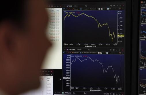 A journalist looks at a screen in this illustration photo that shows graphics representing the losses in the French CAC 40 (Top) and German DAX (Bottom) stock indexes in Paris, France, August 24, 2015. Trading screens flashed red across Europe as stock markets in Frankfurt and Paris fell, while Athens' bourse - already down sharply due to Greece's debt problems - slumped around 10 percent. REUTERS/Regis Duvignau - PM1EB8O18TA01