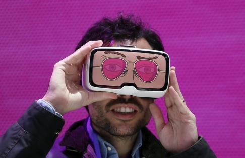 A man tests the 'Zeiss VR One' virtual reality glasses during the Mobile World Congress in Barcelona, Spain February 25, 2016. REUTERS/Albert Gea TPX IMAGES OF THE DAY - D1BESPBWXWAA