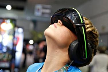 A boy samples the Vuzix iWear video headphones, which are billed as the equivalent to a 125 inch screen viewed from 10 feet, at the E3 Electronic Expo in Los Angeles, California, U.S. June 14, 2016. REUTERS/Lucy Nicholson - S1AETJYEBWAB