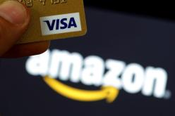 A visa credit card is held in front of an Amazon logo in this picture illustration taken September 6, 2017. REUTERS/Philippe Wojazer/Illustration - RC1B63D6B240