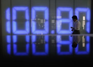 An employee of a foreign exchange company walks past a monitor displaying the Japanese yen's exchange rate against the U.S. dollar in Tokyo May 10, 2013. The dollar remained at a lofty perch against its Japanese counterpart on Friday, after breaking above the 100 yen level in the previous session for the first time since April 2009. REUTERS/Toru Hanai (JAPAN - Tags: BUSINESS TPX IMAGES OF THE DAY) - GM1E95A0OOC01