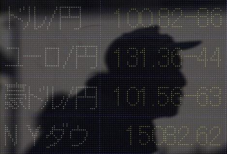 A passerby is reflected in a window displaying the Japanese yen's exchange rate against the U.S. dollar (top) and other major foreign currencies outside a brokerage in Tokyo May 10, 2013. The dollar remained at a lofty perch against its Japanese counterpart on Friday, after breaking above the 100 yen level in the previous session for the first time since April 2009. REUTERS/Issei Kato (JAPAN - Tags: BUSINESS) - GM1E95A0S9002